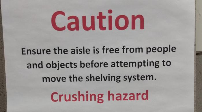 Warning sign on compact shelving: Crushing hazard